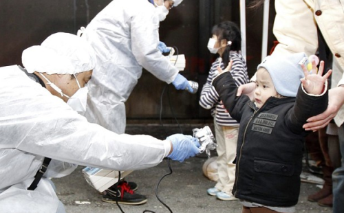 Officials in protective gear check for signs of radiation on children who are from the evacuation area near the Fukushima Daini nuclear plant  Photo: REUTERS/Kim Kyung-Hoon